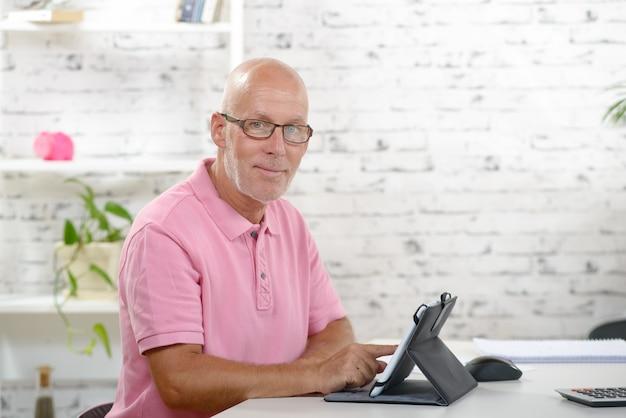 Ein älterer geschäftsmann sieht aus wie ein digitales tablet