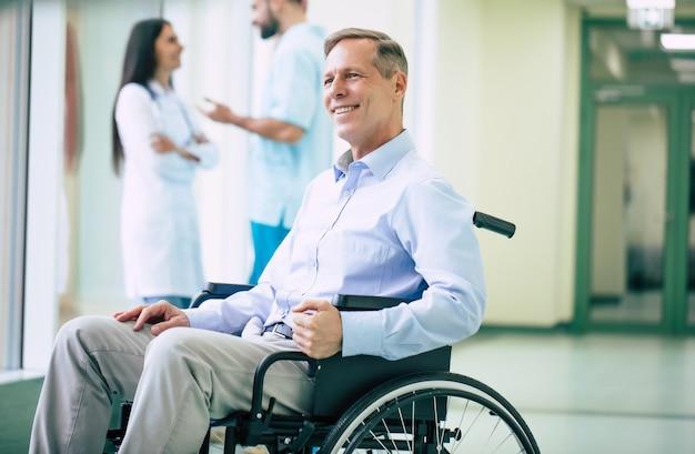 Ein älterer gutaussehender mann im rollstuhl zieht mit hilfe von medizinischem spezialpersonal ins krankenhaus