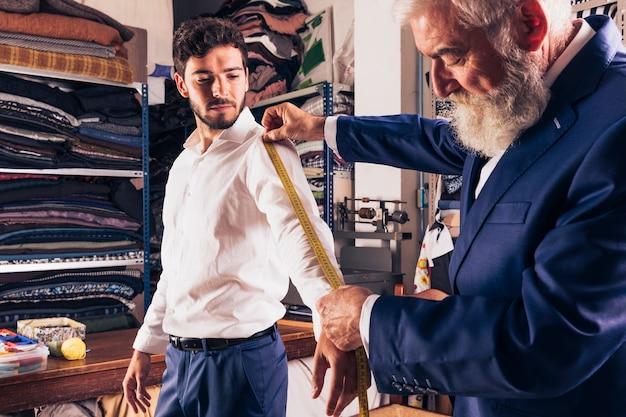 Ein älterer männlicher modedesigner, der maß seiner kundenhülsen nimmt
