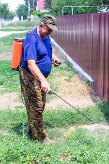 Ein älterer mann besprüht ragweed und andere unkräuter mit chemikalien aus einem sprühgerät auf einer landstraße