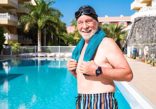 Ein älterer mann, der bereit ist, sport zu treiben und im blauen pool zu schwimmen. mann mit weißem bart und schnurrbart mit badekappe und schutzbrille. ein gesunder lebensstil unter der sonne.