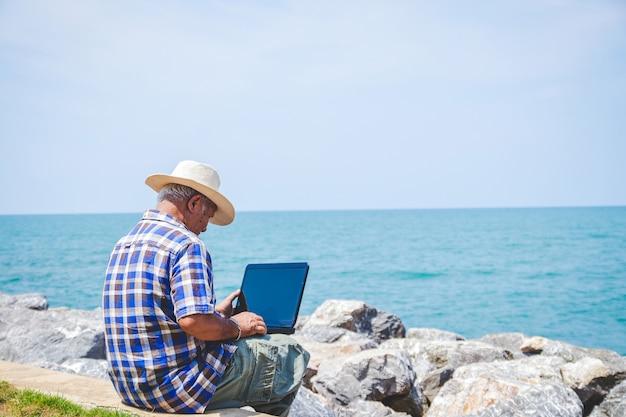 Ein älterer mann, der eine laptop-computer sitzt bei der arbeit durch das meer trägt