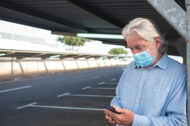 Ein älterer mann, der eine medizinische maske trägt, weil das coronavirus unter der metallstruktur eines verlassenen parkplatzes steht und auf sein smartphone schaut. sonst niemand