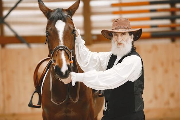 Ein älterer mann, der nahe an einem pferd draußen in der natur steht