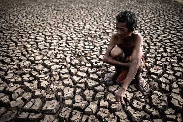 Ein älterer mann, der seine knie umarmend sitzt, verbog sich am unfruchtbaren boden, globale erwärmung
