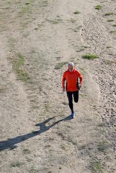 Ein älterer mann in schwarz und grün rennt in den park