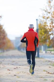Ein älterer mann in schwarz und orange rennt in den park