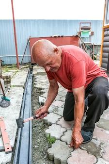Ein älterer mann macht einen fußgängerweg aus pflasterplatten arbeitstätigkeit auf dem hausgrundstück