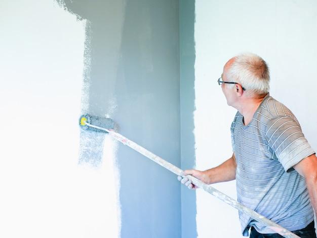 Ein älterer mann malt eine wand mit einer walze. älterer mann macht reparaturen. die wände mit einer walze streichen. altes outfit. grauer wind an einer weißen wand. reparatur zu hause