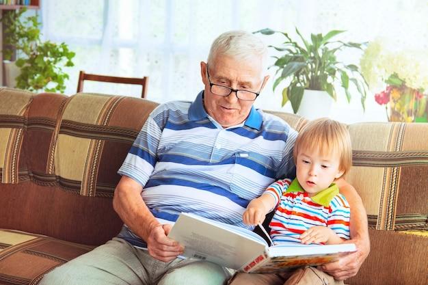 Ein älterer mann mit grauen haaren und brille sitzt mit einem kleinen jungen auf einem sofa und hält ein buch in der hand. ein großvater liest seinem enkel ein märchen vor.