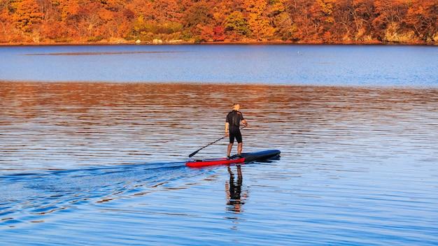 Ein älterer mann reitet in der ruhigen see auf einem aufblasbaren sup-board vor dem hintergrund der fernöstlichen herbstküste