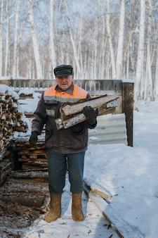Ein älterer mann sammelt im winter brennholz in einem russischen dorf.