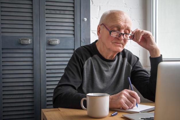 Ein älterer mann schaut auf den laptopbildschirm, macht notizen in einem notizbuch, schreibt steuern.