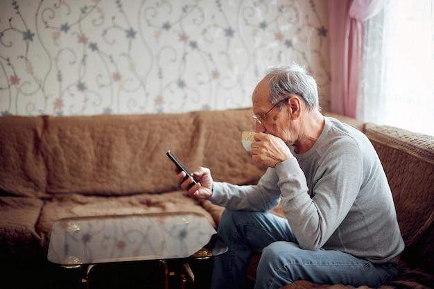 Ein älterer mann trinkt morgentee und überprüft seine e-mails auf seinem smartphone