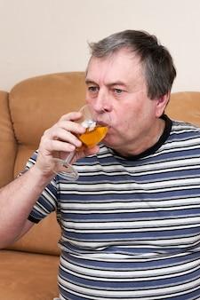 Ein älterer mann trinkt weißwein, während er auf der couch sitzt