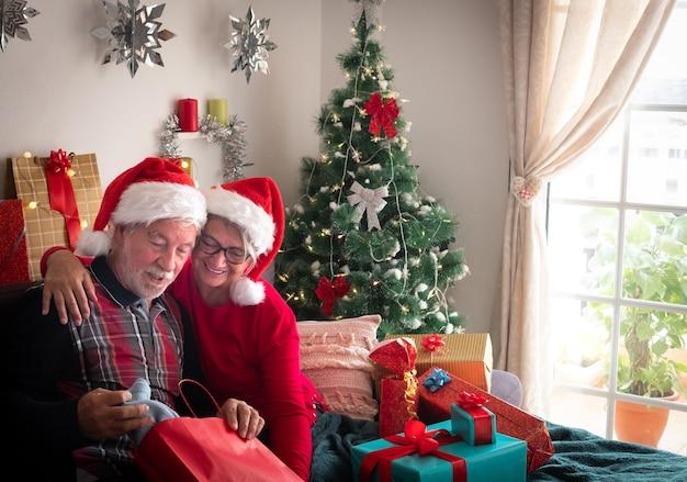Ein älterer mann überrascht über den blauen pullover, den er als weihnachtsgeschenk erhalten hat umarmung und lächelt. familien- und liebeskonzept. weihnachtsbaum im hintergrund