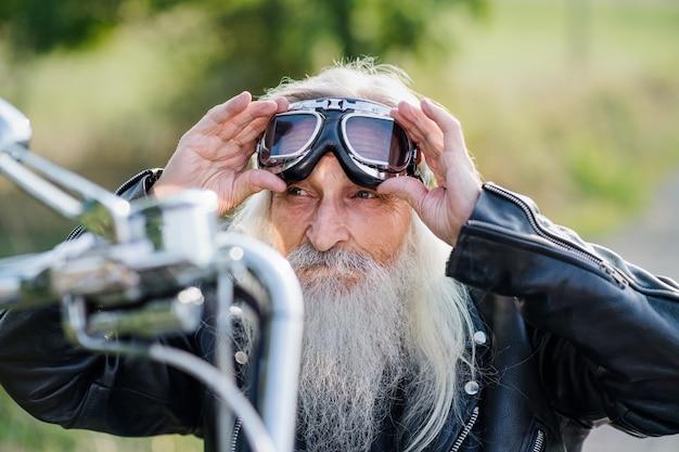 Ein älterer reisender mit motorrad und brille auf der straße auf dem land.