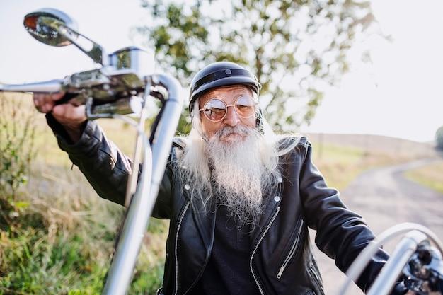 Ein älterer reisender mit motorrad und sonnenbrille in der landschaft, blick in die kamera.