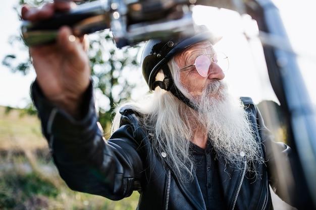 Ein älterer reisender mit motorrad und sonnenbrille in der landschaft.