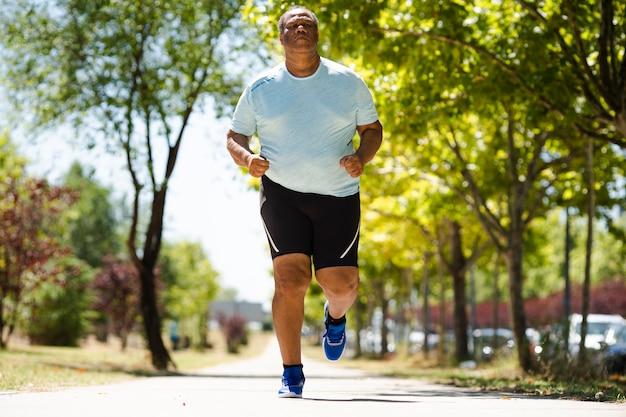 Ein älterer schwarzer mann rennt im park und bemüht sich sehr, übergewicht abzubauen