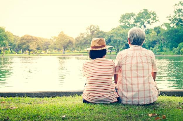 Ein älteres ehepaar, das sich mit liebe und glück in einem park mit einem großen teich umarmt.