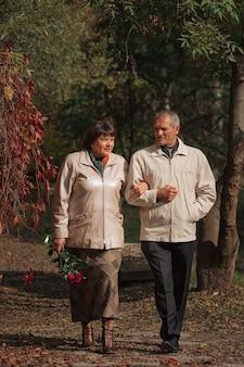 Ein älteres ehepaar geht in einem herbstpark händchen haltend und hält einen strauß roter rosen.