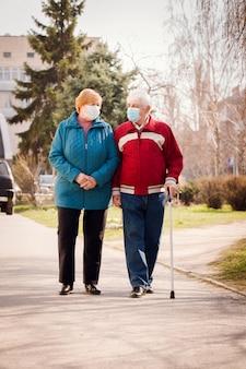 Ein älteres ehepaar in schutzmasken geht die straße entlang