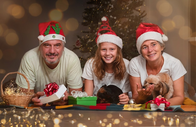Ein älteres ehepaar mit einem teenager tauscht geschenke zu weihnachten aus. porträt einer glücklichen familie nahe dem weihnachtsbaum
