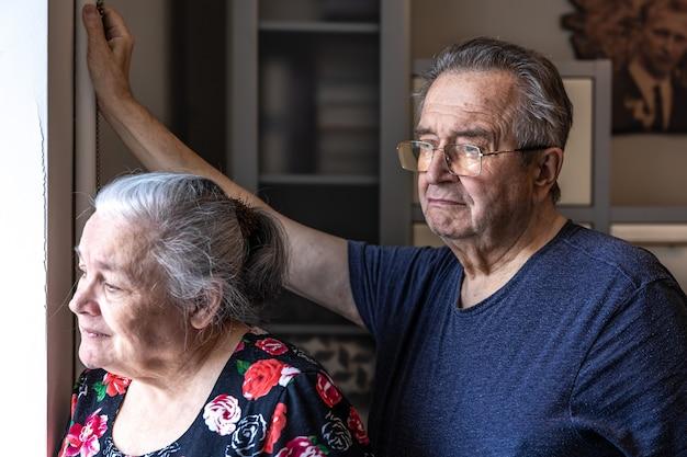 Ein älteres ehepaar steht am fenster und schaut auf jemanden.