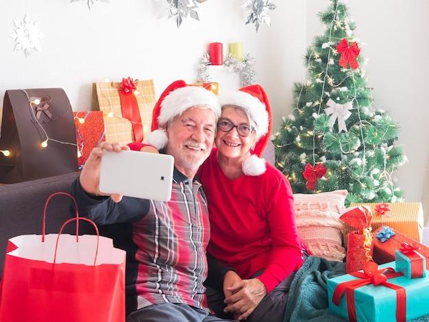 Ein älteres paar von leuten lächelt glücklich und schaut auf das handy nach einem selfie. weihnachtsmütze tragen. weihnachtsbaum im hintergrund. weiße wand