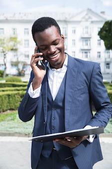 Ein afrikanischer junger geschäftsmann, der das klemmbrett spricht am handy betrachtet