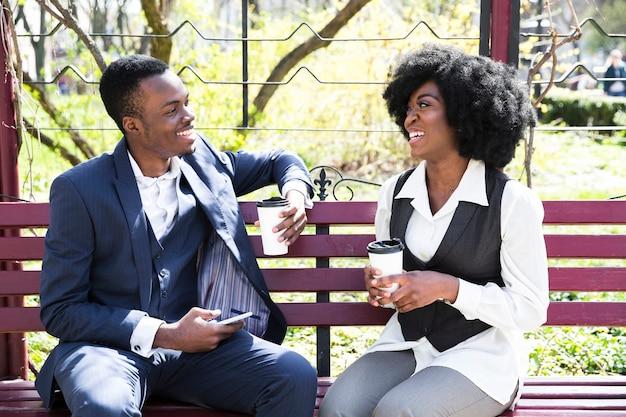 Ein afrikanischer junger geschäftsmann und eine geschäftsfrau, die auf der bank hält wegwerfkaffeetasse sitzen