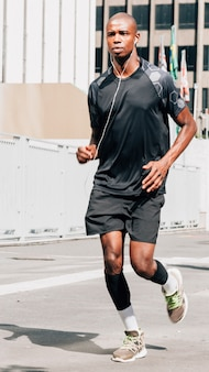 Ein afrikanischer junger männlicher athlet, der auf hörender musik der straße auf kopfhörer läuft