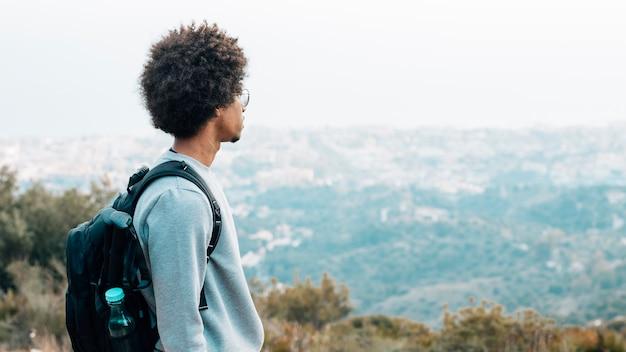 Ein afrikanischer junger männlicher wanderer mit seinem rucksack, der ansicht betrachtet