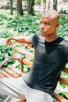 Ein afrikanischer junger mann, der auf der bank im garten sitzt