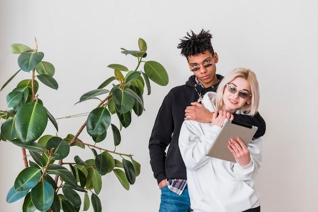 Ein afrikanischer junger mann, der hinter ihrer freundin betrachtet digitale tablette steht