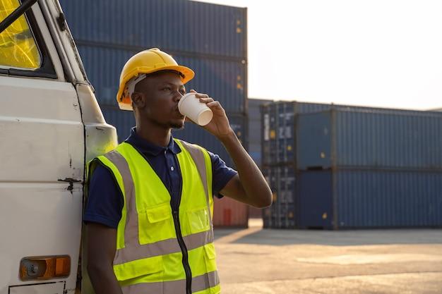 Ein afrikanischer lastwagenfahrer stand ruhend und glücklich lächelnd neben dem lastwagen. im containerlager