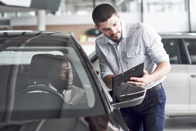 Ein afrikanischer mann, der ein neues auto kauft, überprüft ein auto und spricht mit einem professionellen verkäufer.