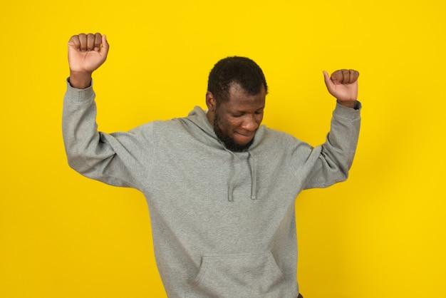Ein afroamerikaner, der ein graues sweatshirt trägt, tanzt und posiert auf einer gelben wand.