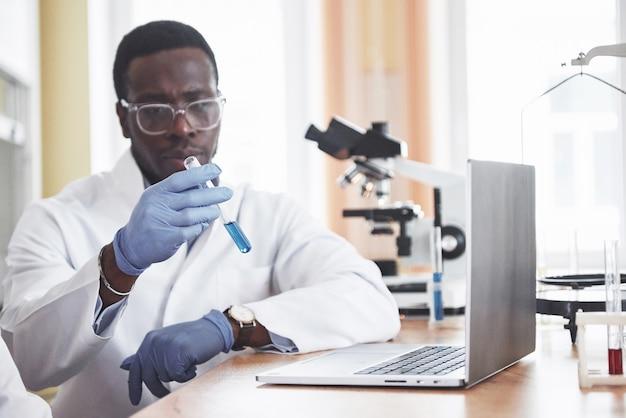 Ein afroamerikanischer arbeiter arbeitet in einem labor und führt experimente durch.