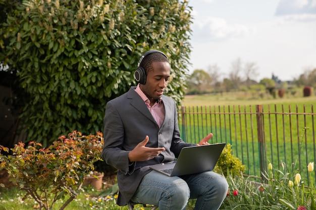Ein afroamerikanischer geschäftsmann trägt während eines arbeitsvideoanrufs seine kopfhörer und spricht im freien in einem garten.