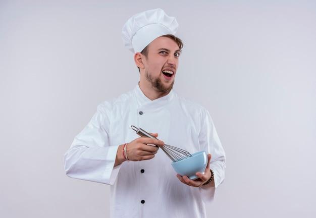 Ein aggressiver junger bärtiger kochmann, der weiße kochuniform und hut hält mischerlöffel auf blauer schüssel, während auf einer weißen wand schauend