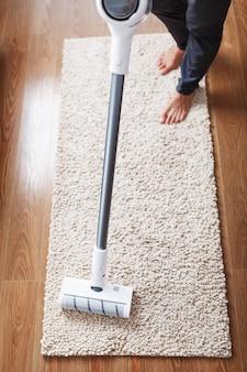 Ein akku-staubsauger reinigt den teppich im wohnzimmer mit der unterseite der beine
