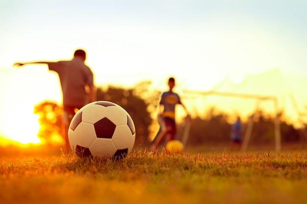 Ein aktionssportbild einer gruppe kinder, die fußballfußball für übung im ländlichen gemeinschaftsgebiet unter dem sonnenuntergang spielen