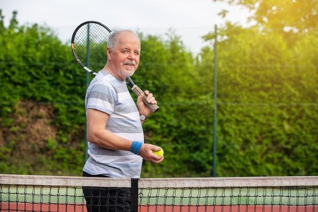 Ein aktiver rentnermann, der draußen tennis spielt und schönen sommertag genießt