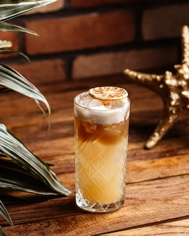 Ein alkoholcocktail von vorne in glas auf dem braunen holzschreibtisch