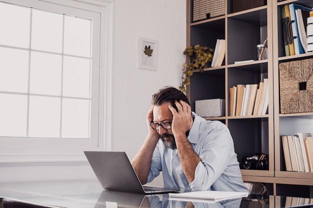 Ein alleiner unglücklicher und trauriger mann zu hause im büro, der einen laptop benutzt und ihn mit den händen im kopf betrachtet. gestresster mann in schwierigkeiten bei der lösung eines problems