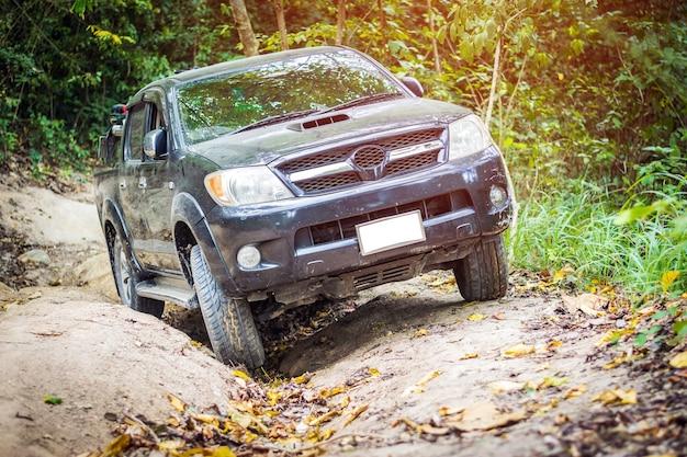 Ein allradantrieb klettert auf einer schwierigen offroad in bergwäldern in thailand.