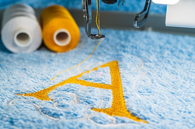 Ein alphabetentwurf auf tuch im band der stickmaschine