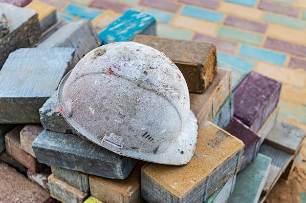 Ein alter arbeitshelm ruht auf gefalteten pflastersteinen. ruhepause auf der baustelle. harte arbeit eines baumeisters.